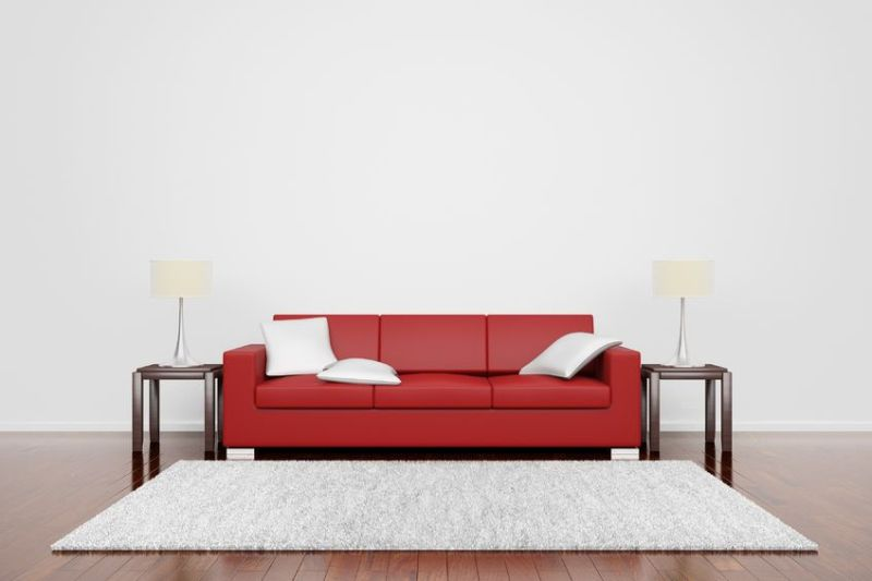 12065689 - red couch on wooden floor with white cushions carpet and lamps