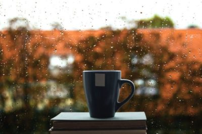 39572421 - books and coffee on window, rain drops on glass in background