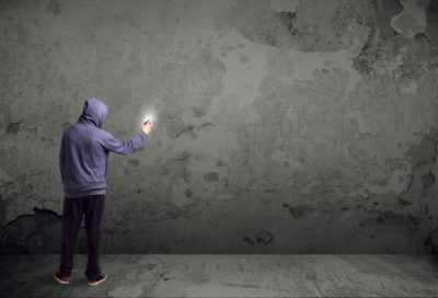 42219423 - young urban painter starting to draw graffiti on the wall