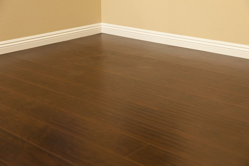 14203151 - beautiful newly installed brown laminate flooring and baseboards in home.