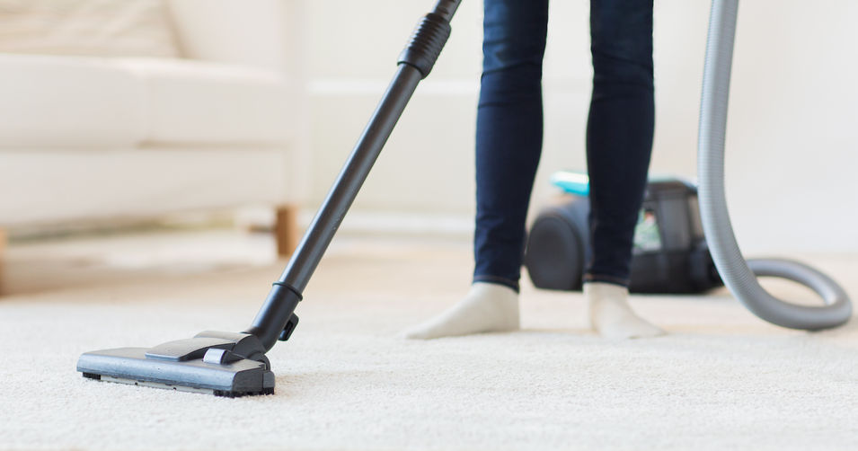 38663110 - people, housework and housekeeping concept - close up of woman with legs vacuum cleaner cleaning carpet at home