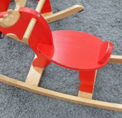 52813445 - children playground, red wooden rocking reindeer or reindeer swing in on a gray rug.