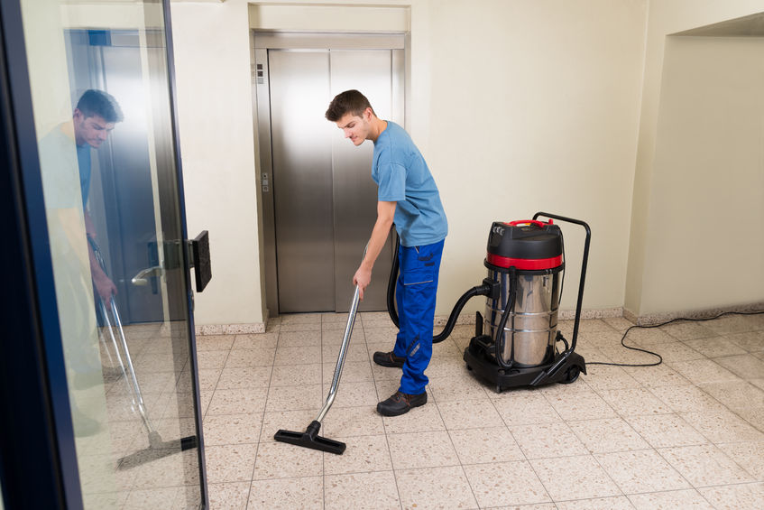 45610025 - happy male worker cleaning floor with vacuum cleaner appliance